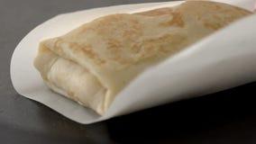 Ο μάγειρας τυλίγει μια τηγανίτα στο έγγραφο για να την δώσει στον πελάτη σε έναν καφέ σε σε αργή κίνηση φιλμ μικρού μήκους