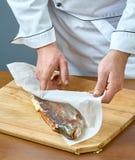 Ο μάγειρας τυλίγει τα ψάρια σε ένα έγγραφο για το ψήσιμο μιας πλήρους συλλογής των συνταγών τροφίμων Στοκ Εικόνα