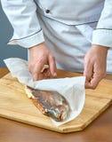 Ο μάγειρας τυλίγει τα ψάρια σε ένα έγγραφο για το ψήσιμο μιας πλήρους συλλογής των συνταγών τροφίμων Στοκ φωτογραφία με δικαίωμα ελεύθερης χρήσης