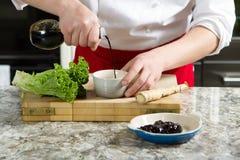 Ο μάγειρας χύνει τη σάλτσα σε ένα κύπελλο Στοκ Εικόνες