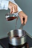 Ο μάγειρας χύνει το κρασί σε ένα τηγάνι για το μαγείρεμα του θερμαμένου κρασιού μια πλήρης συλλογή των μαγειρικών συνταγών Στοκ Εικόνες