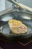 Ο μάγειρας ψήνει το κρέας σε ένα σύνολο σειράς τηγανίσματος παν των συνταγών Στοκ εικόνα με δικαίωμα ελεύθερης χρήσης