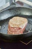 Ο μάγειρας ψήνει το κρέας σε ένα σύνολο σειράς τηγανίσματος παν των συνταγών Στοκ Φωτογραφία