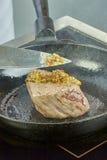Ο μάγειρας ψήνει το κρέας σε ένα σύνολο σειράς τηγανίσματος παν των συνταγών Στοκ φωτογραφία με δικαίωμα ελεύθερης χρήσης