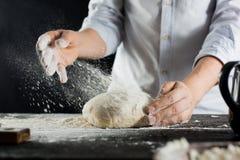 Ο μάγειρας ψεκάζει τη ζύμη με το αλεύρι στον πίνακα κουζινών στοκ φωτογραφίες με δικαίωμα ελεύθερης χρήσης