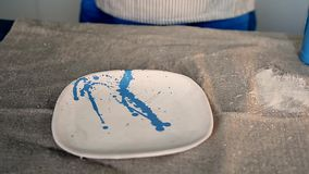 Ο μάγος καταβρέχει το μπλε χρώμα σε ένα άσπρο πιάτο Στον πίνακα με burlap δημιουργικό εργαστήριο απόθεμα βίντεο