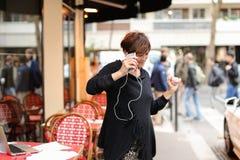 ο μέσης ηλικίας θηλυκός τουρίστας ακούει μουσική από το smartphone και το danci Στοκ Εικόνες