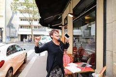 ο μέσης ηλικίας θηλυκός τουρίστας ακούει μουσική από το smartphone και το danci Στοκ εικόνα με δικαίωμα ελεύθερης χρήσης