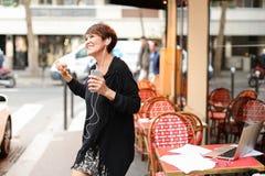ο μέσης ηλικίας θηλυκός τουρίστας ακούει μουσική από το smartphone και το danci Στοκ Εικόνα