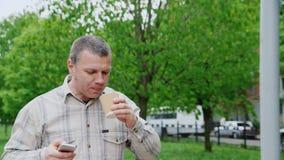 Ο μέσης ηλικίας καφές κατανάλωσης ατόμων πηγαίνει, περπατώντας στο πάρκο πόλεων απόθεμα βίντεο