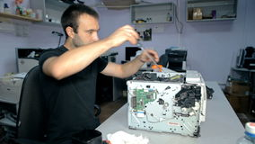 Ο μέσος πυροβοληθείς εργαζόμενος επισκευάζει την ηλεκτρονική ουσία φιλμ μικρού μήκους