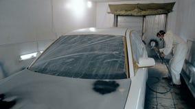 Ο μέσος πυροβοληθείς εργαζόμενος χρωματίζει ένα αυτοκίνητο στο άσπρο χρώμα απόθεμα βίντεο