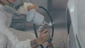 Ο μέσος πυροβοληθείς εργαζόμενος χρωματίζει ένα αυτοκίνητο στο άσπρο χρώμα φιλμ μικρού μήκους