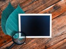 Ο μίνι πίνακας, πιό magnifier και βγάζει φύλλα πέρα από το ξύλινο υπόβαθρο Στοκ φωτογραφία με δικαίωμα ελεύθερης χρήσης
