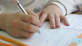 Ο μαθητής γράφει το κείμενο σε ένα εγχειρίδιο με μια μάνδρα απόθεμα βίντεο