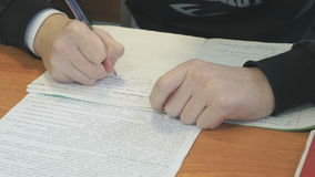 Ο μαθητής γράφει το κείμενο στο βιβλίο άσκησης στο μάθημα απόθεμα βίντεο