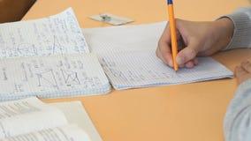 Ο μαθητής γράφει το κείμενο στο βιβλίο άσκησης στο μάθημα φιλμ μικρού μήκους