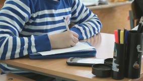 Ο μαθητής γράφει το κείμενο στο φύλλο του εγγράφου απόθεμα βίντεο