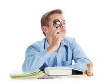 Ο μαθητής διασκέδασης κάθεται κοντά στο γραφείο με τις σχολικές προμήθειες που απομονώνονται στο λευκό Στοκ Φωτογραφία
