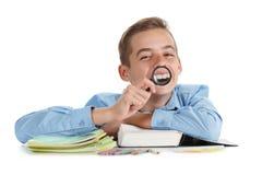 Ο μαθητής διασκέδασης κάθεται κοντά στο γραφείο με τις σχολικές προμήθειες που απομονώνονται στο λευκό Στοκ Εικόνα