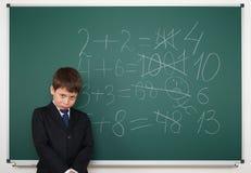 Ο μαθητής κοντά στο σχολικό πίνακα math λύνει Στοκ εικόνες με δικαίωμα ελεύθερης χρήσης