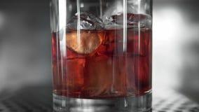 Ο μακρο βλαστός της κόκκινης martini έκχυσης σε ένα σύνολο γυαλιού με έναν πάγο κυβίζει Martini γεμίζει ένα γυαλί με τον πάγο Κατ φιλμ μικρού μήκους