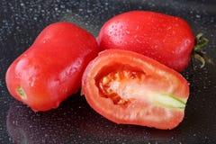 Ο μακρο πυροβολισμός δύο και οι κατά το ήμισυ τεμαχισμένες οργανικές ρόδινες ντομάτες δαμάσκηνων σε ένα μαύρο υπόβαθρο με το νερό Στοκ εικόνα με δικαίωμα ελεύθερης χρήσης