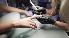 Ο μανικιουρίστας κάνει τη διαδικασία pedicure των επεκτάσεων αποκατάστασης και καρφιών στα καρφιά του κοριτσιού στο σαλόνι καρφιώ απόθεμα βίντεο