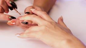 Ο μανικιουρίστας καλύπτει το νύχι γυναικών ` s στο μέσο δάχτυλο του αριστερού χεριού της με ένα καφετί βερνίκι απόθεμα βίντεο