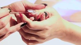 Ο μανικιουρίστας με μια λεπτή βούρτσα χρωματίζει το καρφί του αντίχειρα στο αριστερό χέρι με μια λάκκα με τα σπινθηρίσματα φιλμ μικρού μήκους