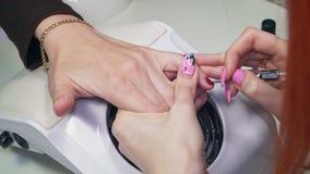 Ο μανικιουρίστας χρωματίζει τα καρφιά με μια πολύ λεπτή βούρτσα απόθεμα βίντεο