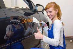 Ο μαρκάροντας ειδικός αυτοκινήτων βάζει το λογότυπο με την τυλίγοντας ταινία αυτοκινήτων στο αυτοκίνητο στοκ εικόνες με δικαίωμα ελεύθερης χρήσης