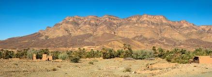 Ο μαροκινός άργιλος στεγάζει κοντά στα βουνά και τους φοίνικες Στοκ φωτογραφία με δικαίωμα ελεύθερης χρήσης
