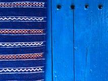 Ο μαροκινός τάπητας σε μια μπλε πόρτα μέσα η μπλε πόλη στο Μαρόκο Στοκ Εικόνες