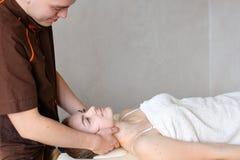 Ο μασέρ τύπων με τα ισχυρά χέρια ζυμώνει το λαιμό του νέου κοριτσιού, τα οποία βρίσκονται Στοκ Εικόνες