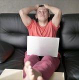 Ο ματαιωμένος νεαρός άνδρας κάθεται κοντά σε ένα lap-top στο καθιστικό της στοκ εικόνες