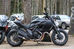 Ο ματ Μαύρος Ducati Diavel μοτοσικλετών Άποψη δεξιά πλευρών στα πλαίσια των αυτοκινήτων και των δέντρων μια νεφελώδη ημέρα στοκ εικόνα