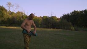 Ο μαυρισμένος νέος γιόγκη βάζει την κουβέρτα για τις κατηγορίες γιόγκας στο ξέφωτο στο πάρκο πόλεων απόθεμα βίντεο