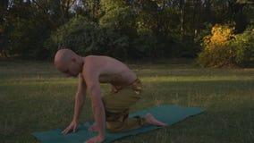Ο μαυρισμένος τύπος με το γυμνό κορμό εκτελεί τη γιόγκα Asanas, ασκεί τη συστροφή το πρωί στο πάρκο πόλεων φιλμ μικρού μήκους
