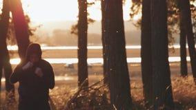 Ο μαχητής ατόμων sportswear στο τρέξιμο και εκπληρώνει το λάκτισμα στο δάσος φθινοπώρου φιλμ μικρού μήκους
