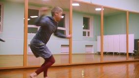 Ο μαχητής εκτελεί τα αρειανά τεχνάσματα με τα στοιχεία χορού στην αθλητική γυμναστική απόθεμα βίντεο