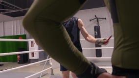 Ο μαχητής πηδά στο άλμα του σχοινιού στη θέση κοντά στο ριγκ, εκπαιδευτικός με τον προσωπικό εκπαιδευτή φιλμ μικρού μήκους