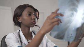 Ο μαύρος θηλυκός γιατρός κάθεται σε ένα γραφείο γραφείων κοιτάζοντας στη κάμερα, εργασία νοσοκόμων αφροαμερικάνων στο lap-top στο φιλμ μικρού μήκους