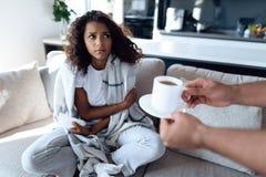 Ο μαύρος και η γυναίκα κάθονται στον καναπέ Η γυναίκα έχει ένα κρύο και ο άνδρας έφερε το καυτό τσάι της Στοκ φωτογραφίες με δικαίωμα ελεύθερης χρήσης