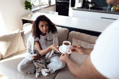 Ο μαύρος και η γυναίκα κάθονται στον καναπέ Η γυναίκα έχει ένα κρύο και ο άνδρας έφερε το καυτό τσάι της Στοκ Φωτογραφίες