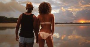 Ο μαύρος και η γυναίκα κρατούν τα χέρια εξετάζοντας έξω το γραφικούς ηλιοβασίλεμα και τον ορίζοντα στοκ εικόνες