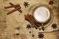 Ο Μαύρος καφέ με το γάλα, κανέλα, γλυκάνισο σε έναν παλαιό πίνακα επάνω από την όψη Στοκ φωτογραφία με δικαίωμα ελεύθερης χρήσης