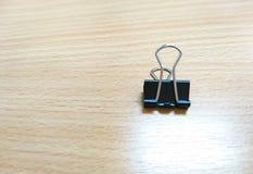 Ο μαύρος συνδετήρας συνδέσμων που βρίσκεται στον ξύλινο πίνακα στοκ εικόνες με δικαίωμα ελεύθερης χρήσης