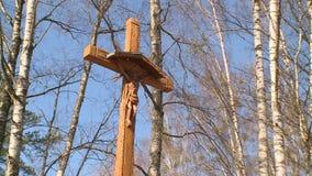 Ο μεγάλος ξύλινος σταυρός στέκεται μεταξύ των δέντρων στο υπόβαθρο του μπλε ουρανού απόθεμα βίντεο