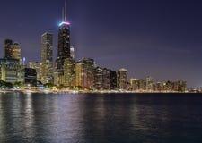 Ο μεγάλος ορίζοντας πόλεων τη νύχτα με τα φω'τα άναψε επάνω κατά μήκος της ακτής νερού στοκ εικόνες